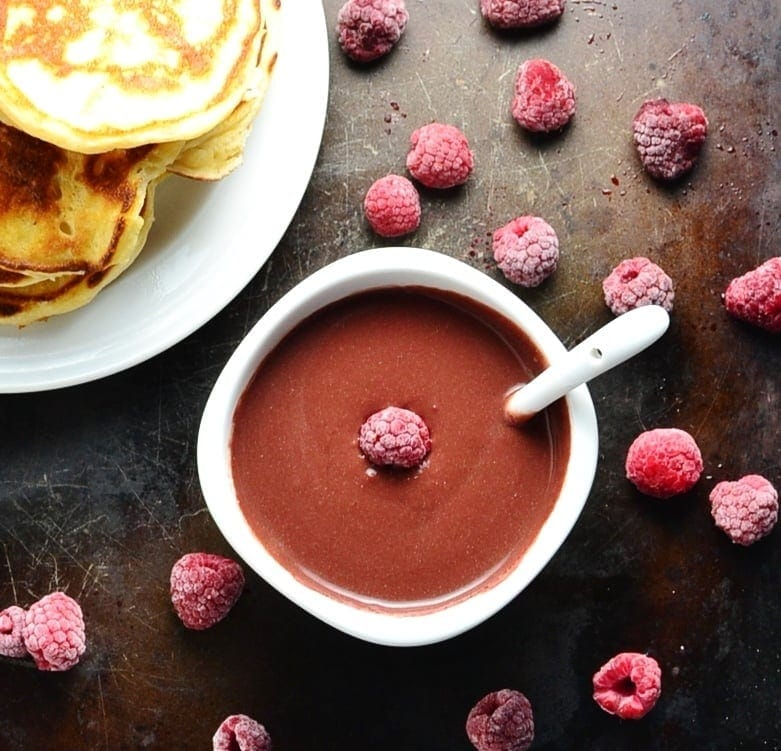 Chocolate sauce with raspberries in white bowl with spoon, with partial view of white plate with pancakes on dark surface.