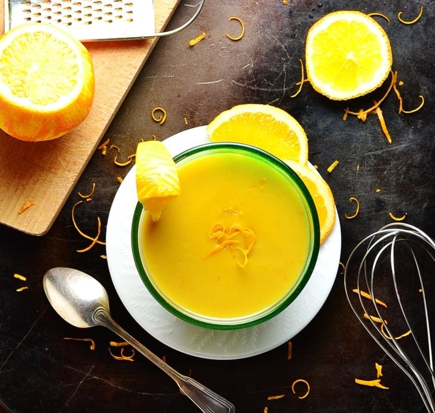 Orange sauce in bowl on white plate with cutting board, oranges, zester, spoon, whisk and orange zest on dark brown surface.