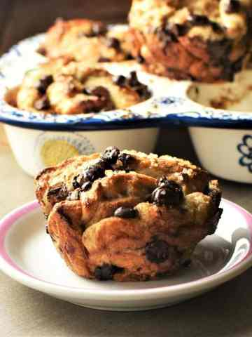 Side view of french toast muffin on small plate with muffins in pan in background.