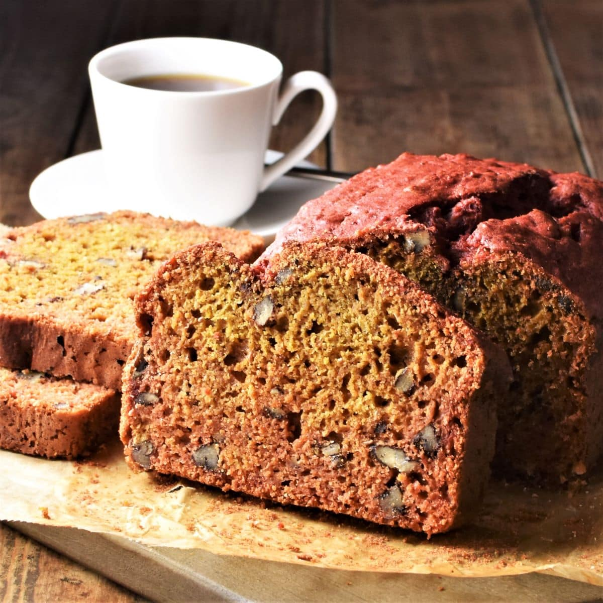 Side view of beetroot bread on top of parchment and cup of coffee in background.