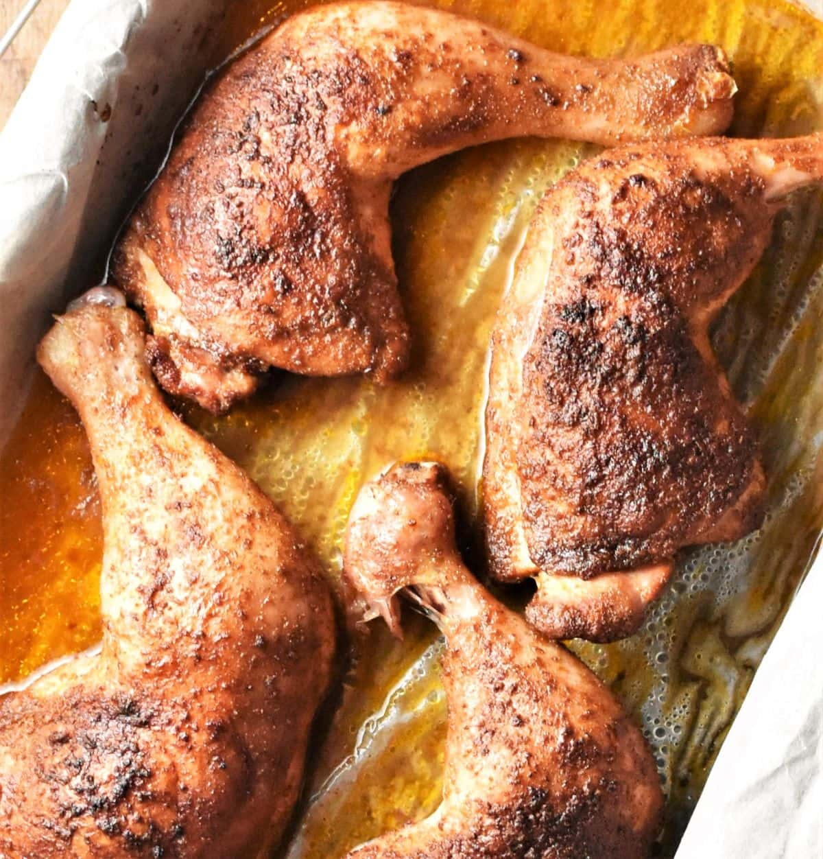 Close-up view of 4 crispy chicken legs in roasting pan.