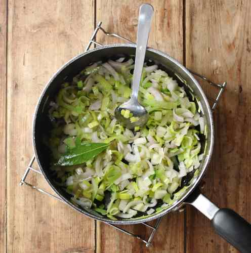 Chopped leek and onion with bay leaf and spoon in large pot.