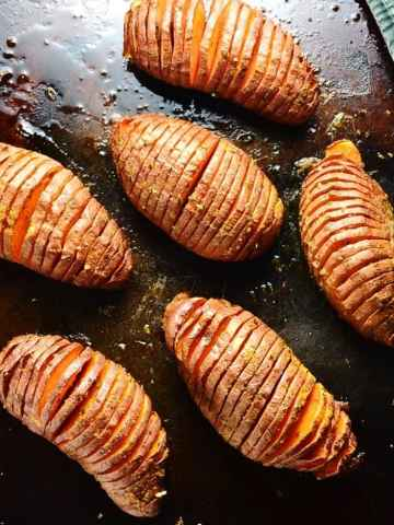 Hasselback sweet potatoes on dark brown oven tray.