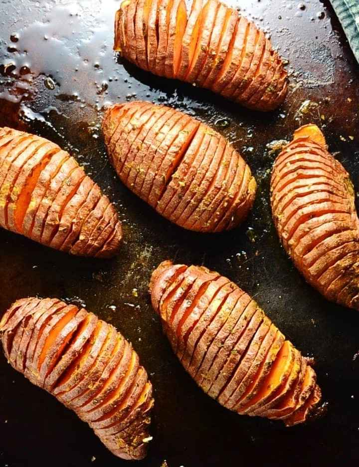 Hasselback sweet potatoes on dark brown oven tray.