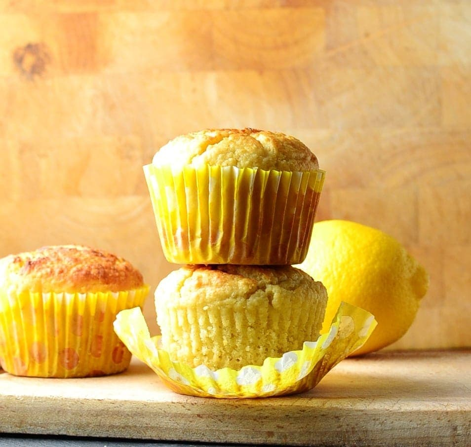 Breakfast recipes for Easter - two marzipan muffins one on top of the other with lemon in background on wooden tray.
