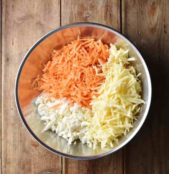 Grated sweet potato, cheese and chopped cauliflower in large metal bowl.