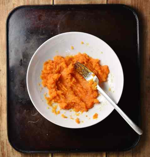 Top down view of mashed sweet potato in white bowl with fork.