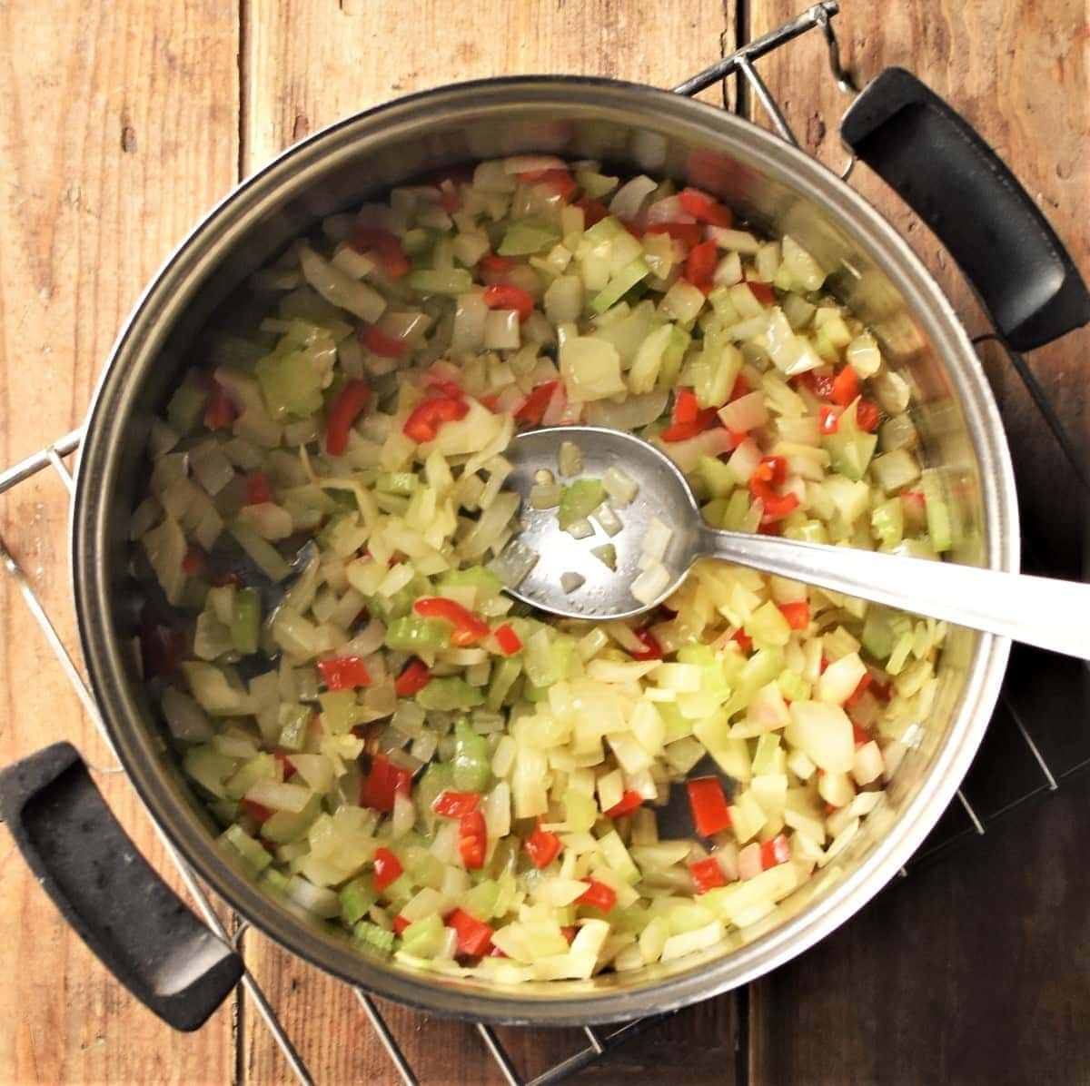 Stewed onion, celery and pepper in saucepan with spoon.