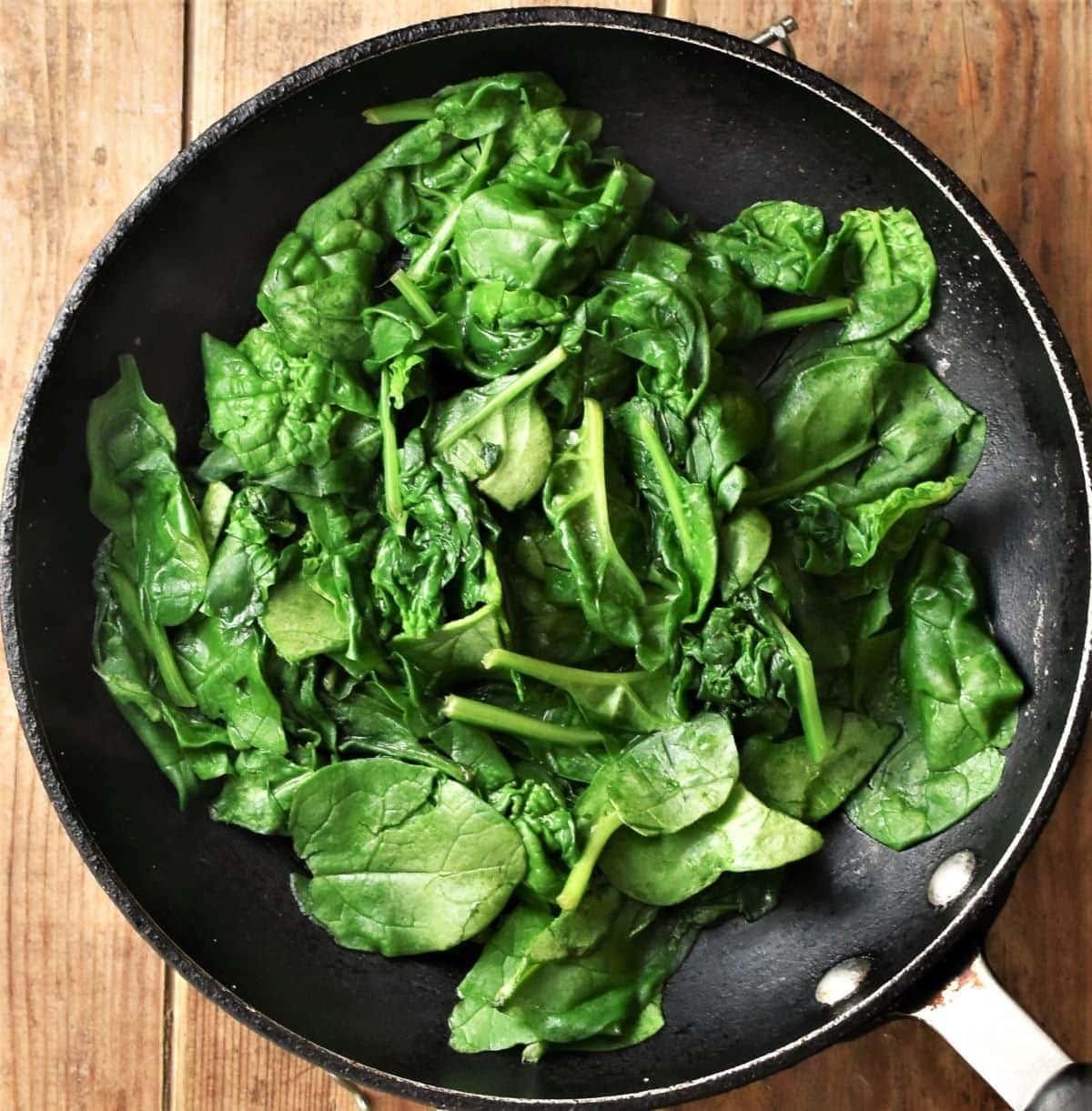 Fresh spinach, partly wilted, in skillet
