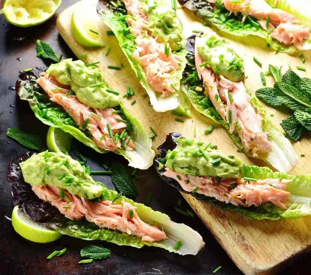 Lettuce wraps with salmon and guacamole with garnish of herbs and lime wedges on top of wooden board and dark table.