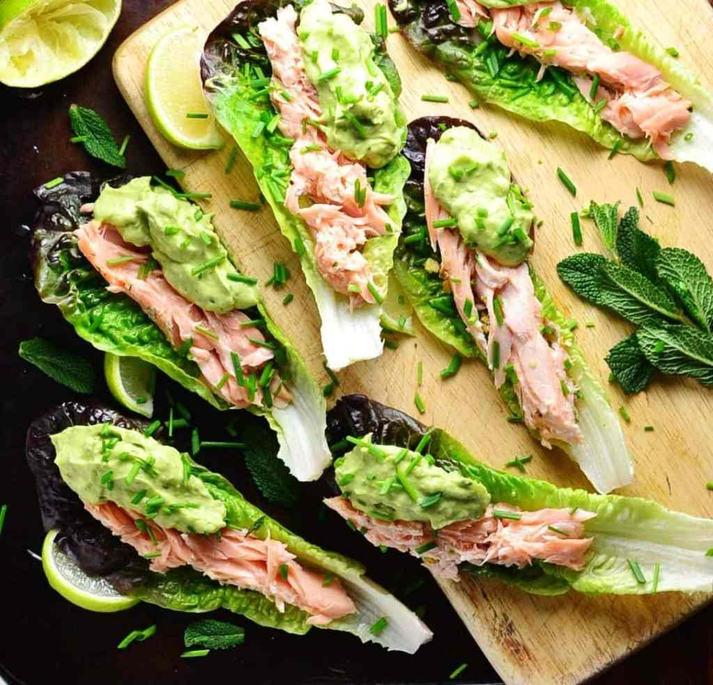 Top down view of lettuce wraps with salmon and guacamole with lime wedges and garnish of herbs on top of wooden board and dark table.