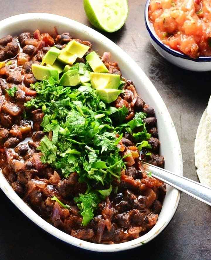 Black bean stew in white oval dish garnished with chopped cilantro, avocado and nachos, with lime, salsa in blue dish and tortilla on dark brown surface.
