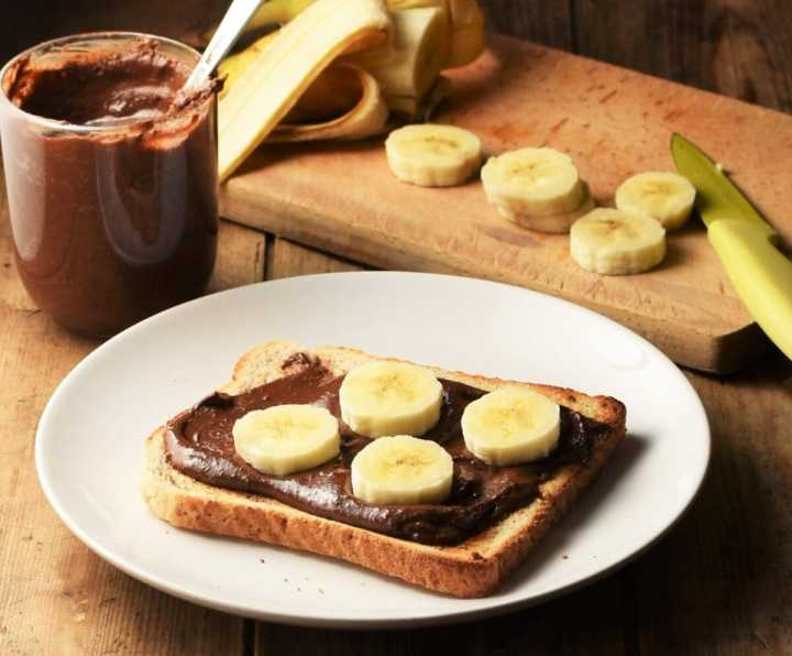 Side view of chocolate spread on toast with banana on white plate, spread in cup and chopped banana in background.