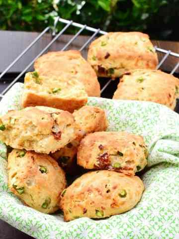 Sun dried tomato scones in basket lined with green cloth and cooling rack in backbround.