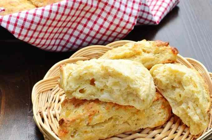 Cauliflower cheese scones in basket with red-and-white checkered cloth with scones in background.