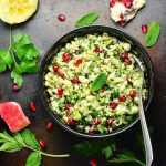 Top down view of roasted cauliflower tabbouleh salad with pomegranate seeds and spoon in black bowl, with herbs and pomegranate seeds scattered around.
