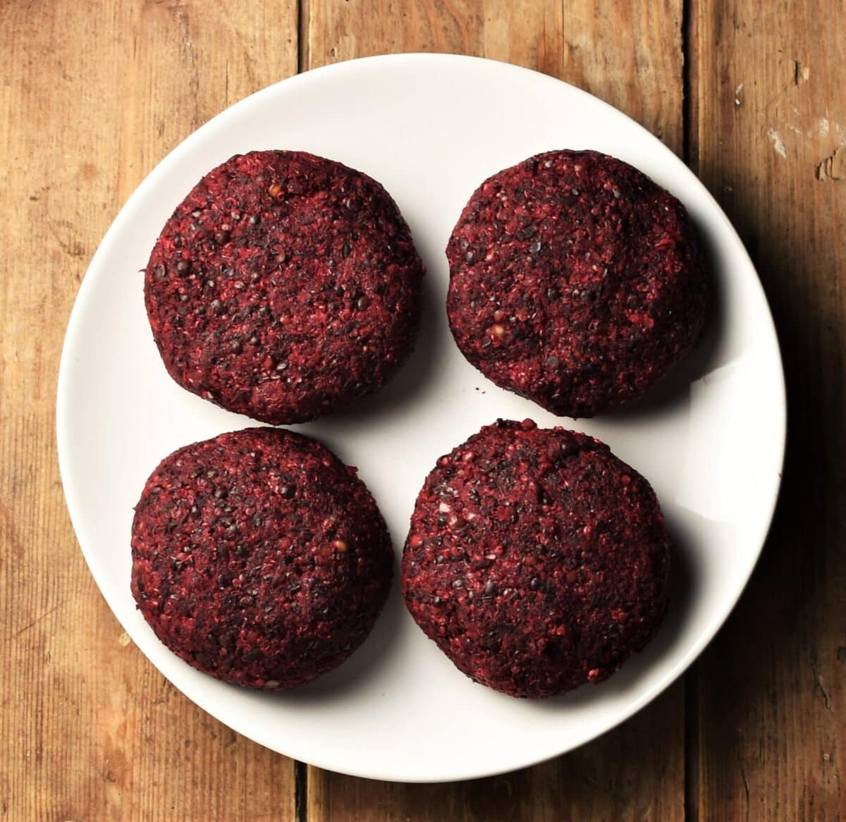 4 uncooked beet quinoa burgers on top of white plate.