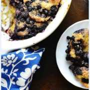 Top down partial view of blueberry french toast casserole in white dish and on white plate with blue-and-white cloth in bottom left corner.