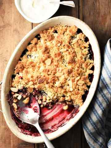 Top down view of cherry crumble in white oval dish with spoon, blue cloth and yogurt in background.