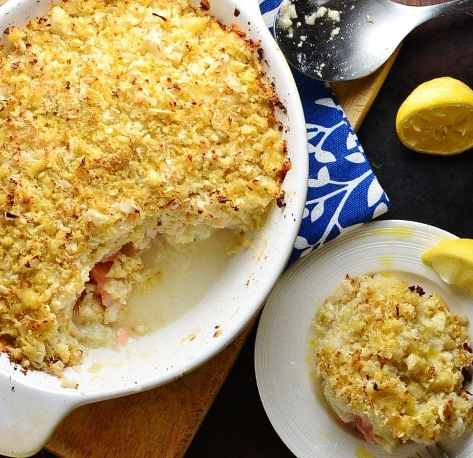 Healthy fish pie with cauliflower topping in white oval casserole dish on wooden board with spoon, lemon, white-and-blue cloth and white plate with pie.
