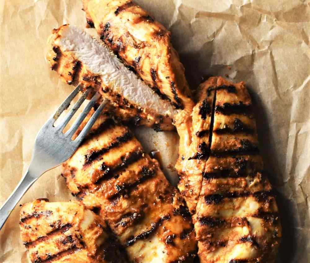 Grilled chicken breast pieces with fork on top of parchment.