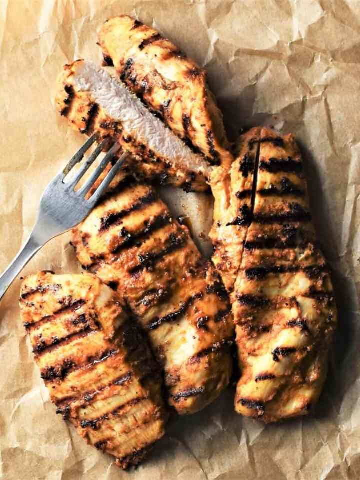 Grilled chicken pieces on top of parchment with fork.