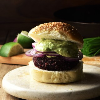 Side view of quinoa beet burger on top of marble plate with lime and chives in background.