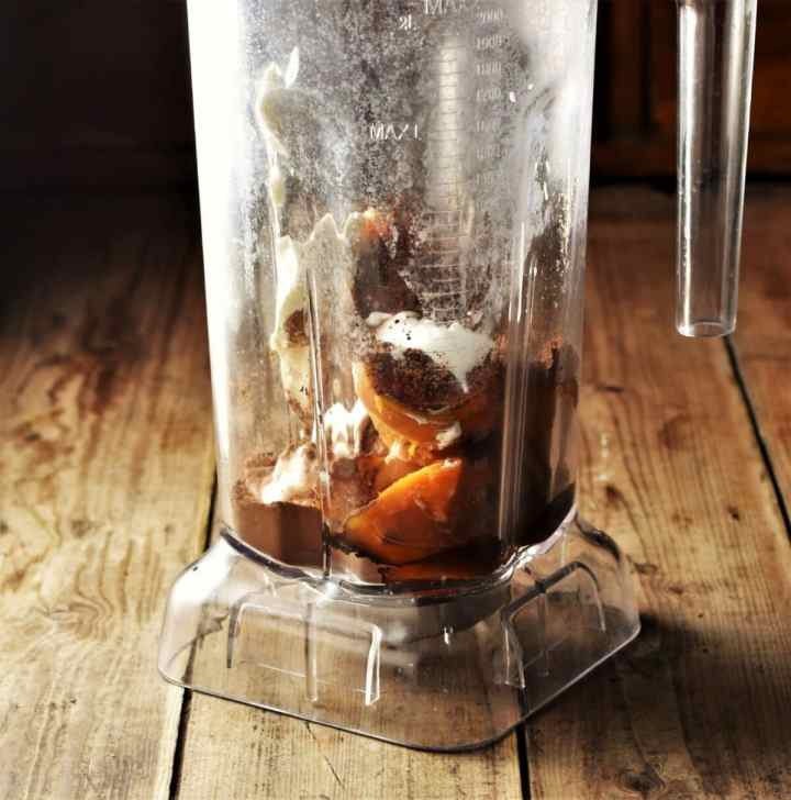 Side view of blender containing chopped sweet potato, cocoa and yogurt.