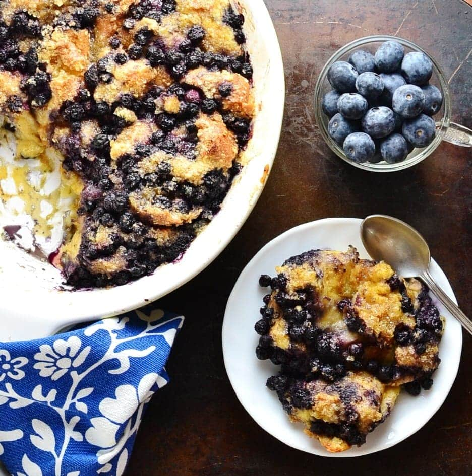 Top down view of blueberry french toast casserole on white plate with spoon, casserole in white oval dish, cup with fresh blueberries and blue-and-white cloth.