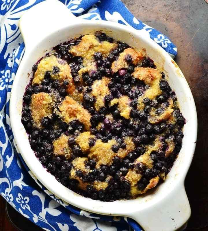 Top down view of blueberry french toast in white oval dish and blue-and-white cloth around it.
