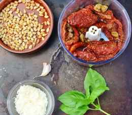 Top down view of sun dried tomatoes in blender, pine nuts in round brown dish, grated cheese in small dish, garlic clove and basil leaves on top of dark metal surface.