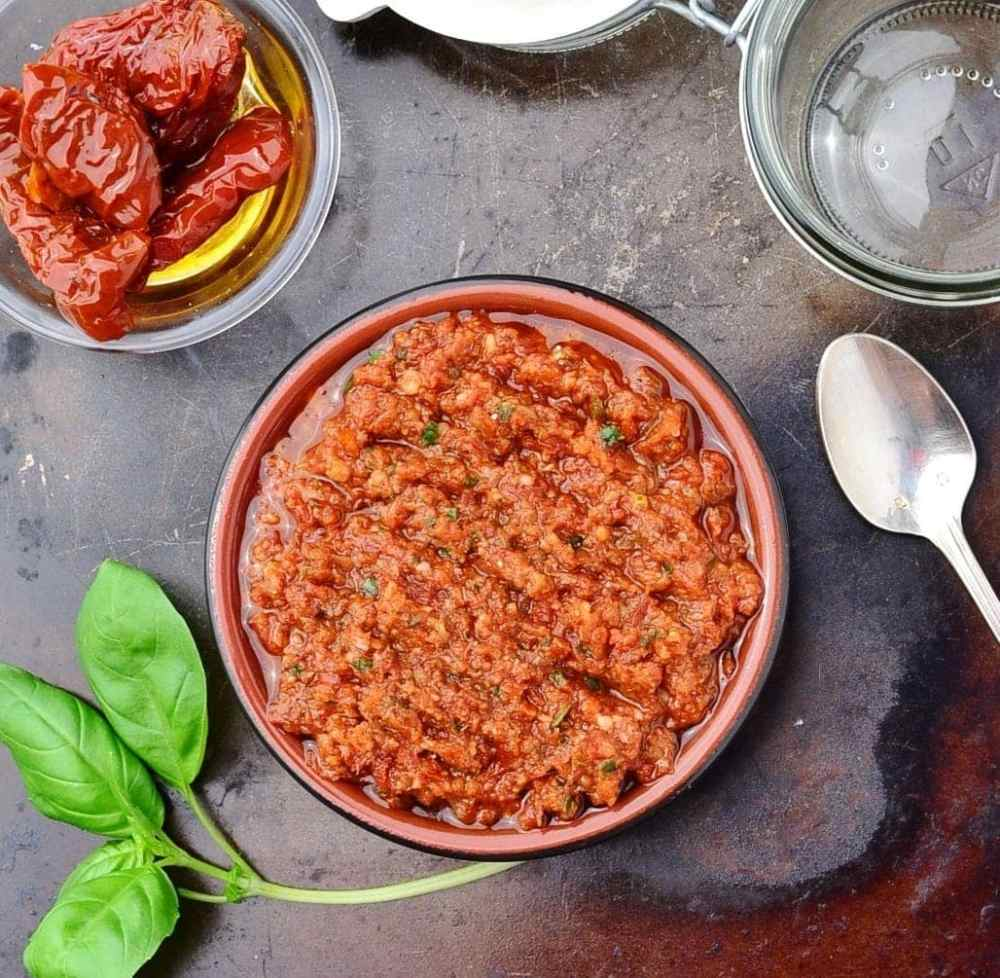 Top down view of sun dried tomato pesto in round dish on top of dark surface with basil leaves, spoon, open jar and sun dried tomatoes in small dish.