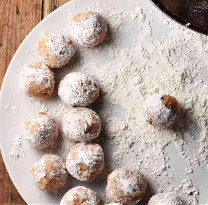 Meatballs rolled in flour on white plate.