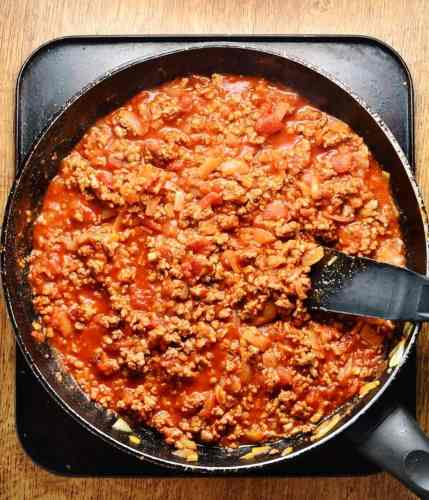 Turkey tomato sauce in pan with black spatula on oven tray.