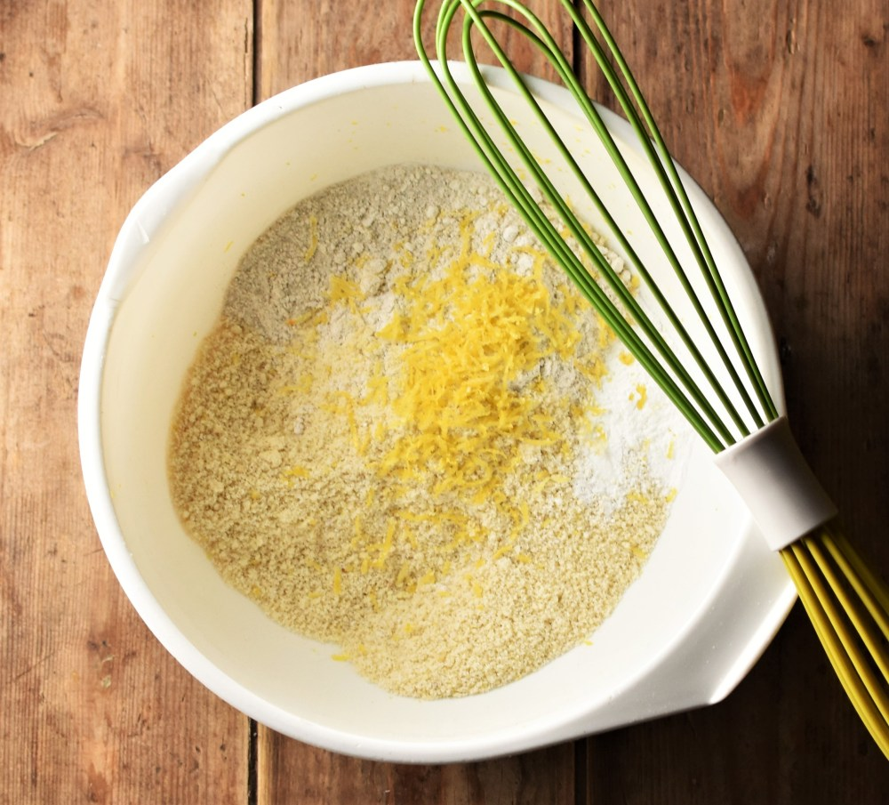 Flour and lemon zest in large white bowl with green whisk.