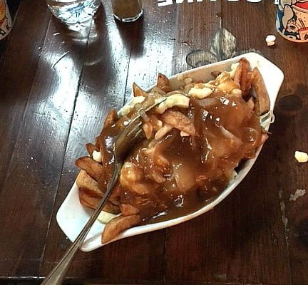Poutine in white oval dish with fork on dark wooden table.