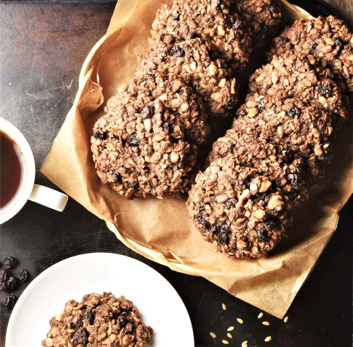 Top down view of chocolate oatmeal cookies on top of parchment and small plate.