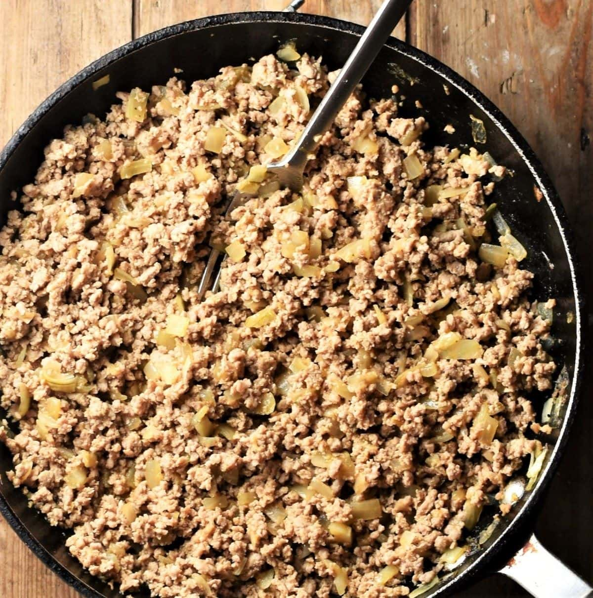 Cooked ground meat with onion mixture in large pan with fork.
