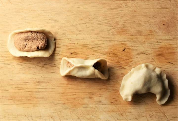 Making pierogi with meat on top of wooden surface.