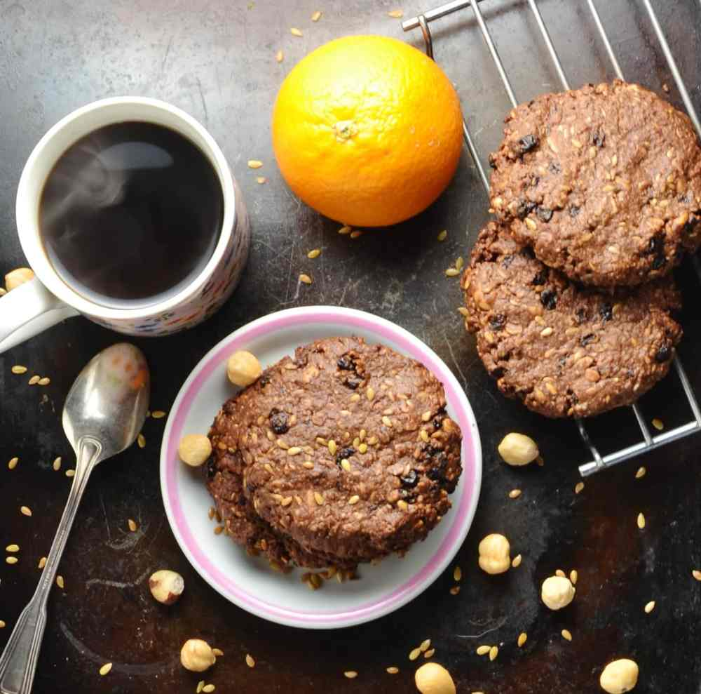 Chocolate oat cookies on small plate and cooling rack, with spoon, orange, hazelnuts and cup of steaming coffee on dark brown surface