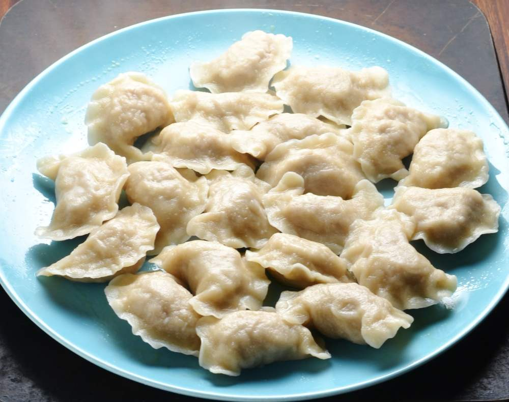 Side view of Polish pierogi on top of blue plate.