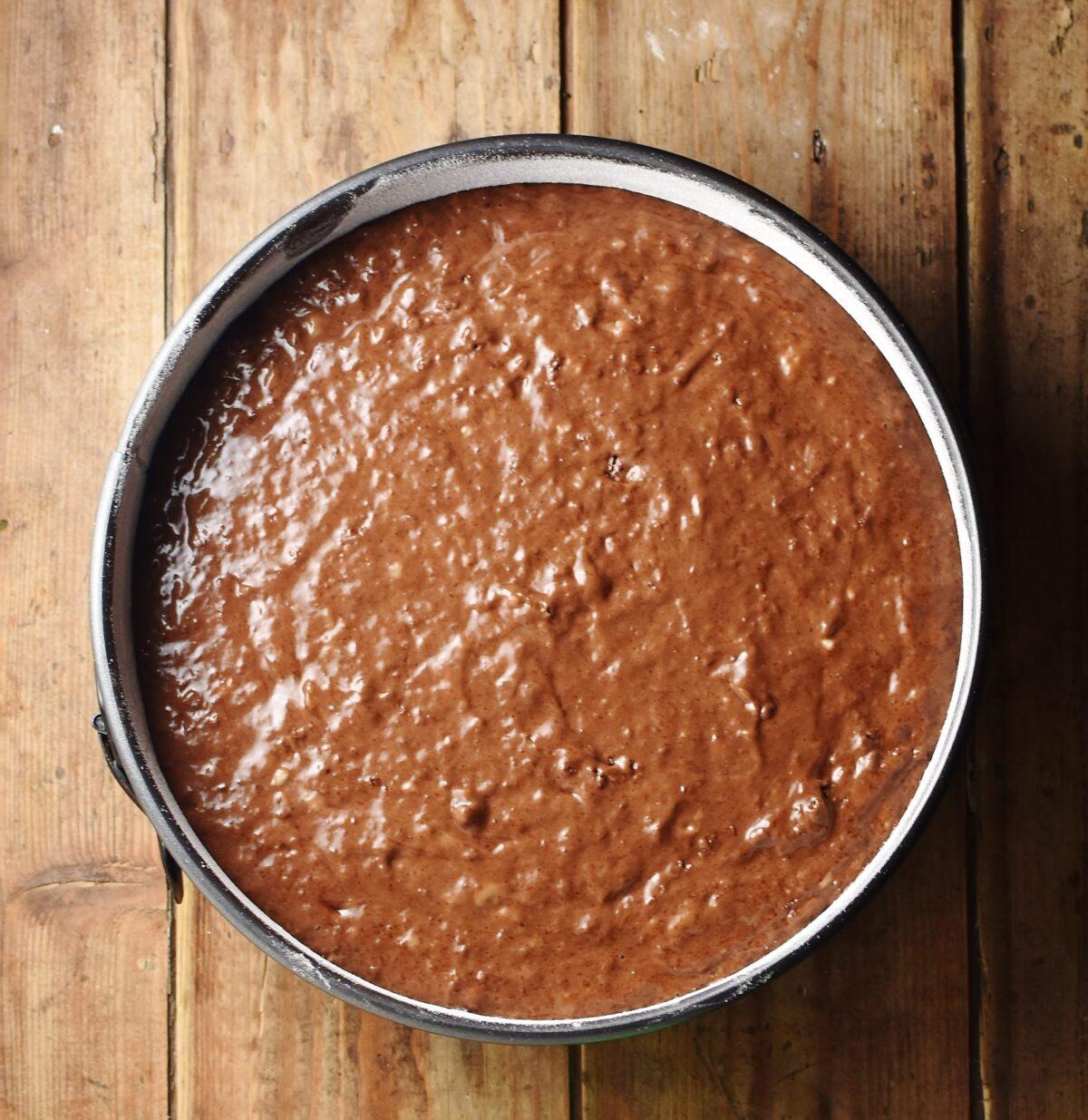 Unbaked chocolate banana cake in round pan.
