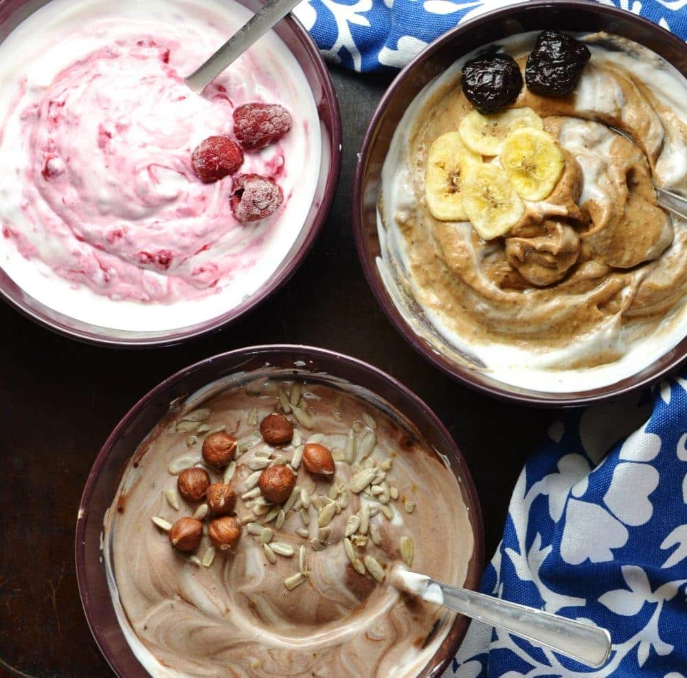 Mocha, raspberry and prune yogurts in separate bowl with spoons, nuts and fruit on top and blue-and-white cloth in background.