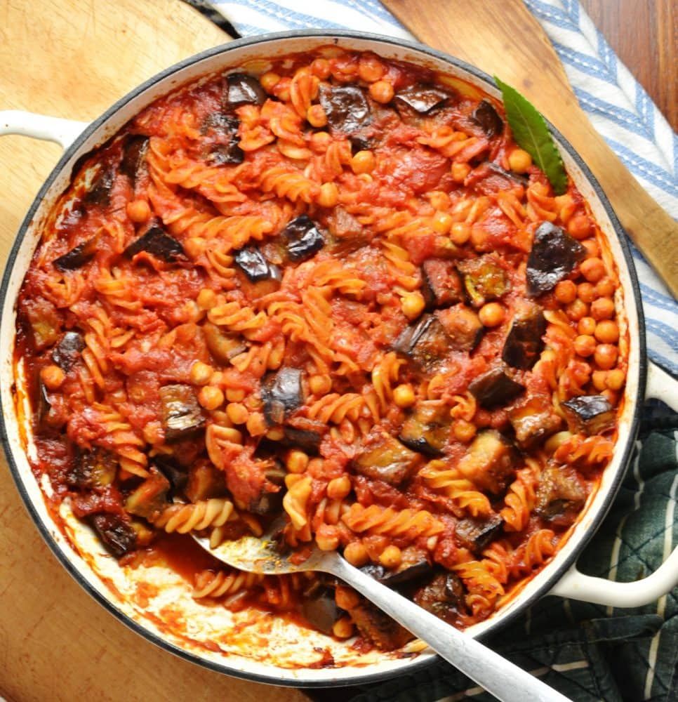 Top down view of fussili pasta in tomato sauce with eggplant pieces and chickpeas, with spoon inside large shallow white dish on top of wooden board.