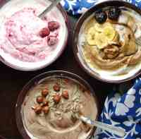 Flavoured mocha, raspberry, prune yogurt in purple bowls with spoons and blue-and-white clothe on dark surface.