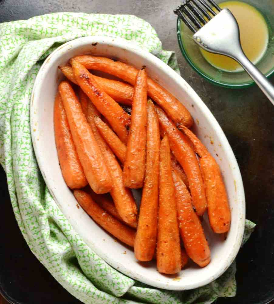 Honey roasted carrots in white oval dish wrapped in green cloth and small dish with dressing and baking brush in top right corner.