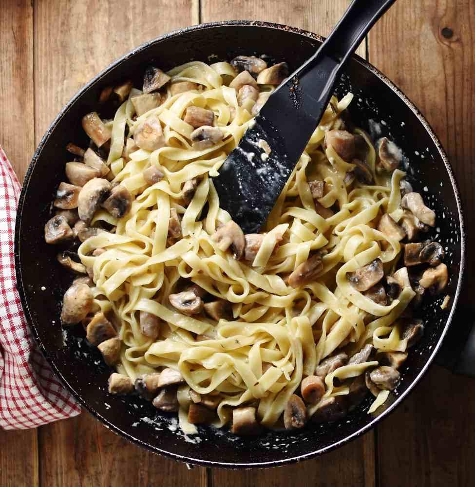 Mushroom pasta with black spatula in large pan.