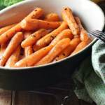 Roasted carrots in oval dish with fork and green cloth to the right, and carrot tops in background.