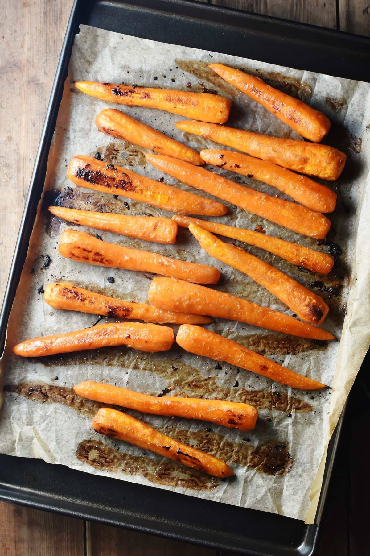 Roasted glazed carrots on top of baking paper.