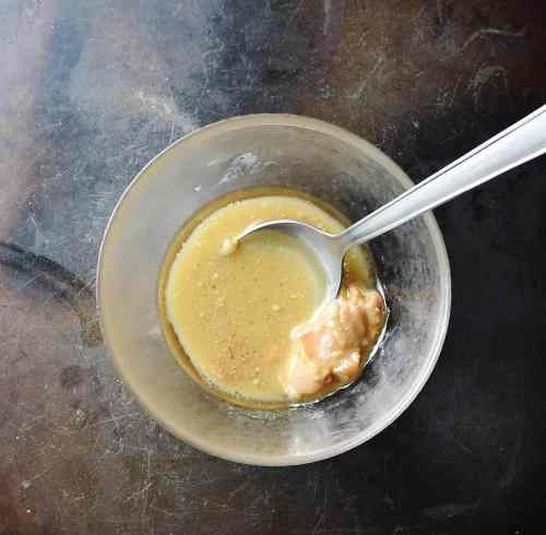 Miso glaze ingredients in small bowl with spoon.